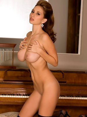 Shay Laren flat on her back on a piano bench licking her boobs.